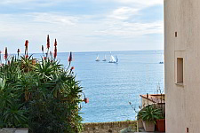 a view of Antibes, from the shore, onto the sea, a few sailing boats